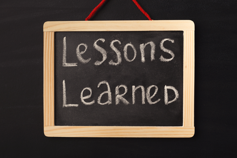 Word lessons learned written on miniature chalkboard in classroom against black background. Lessons, school, education concept.