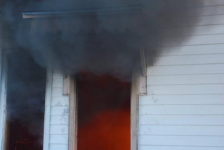 Black smoke billows out of open doorway