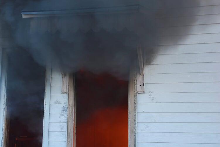 Black smoke billows out of open doorway